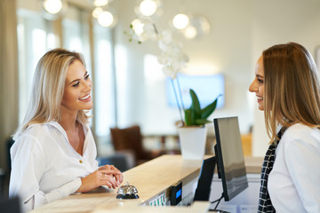 Receptionist and businesswoman at hotel front desk