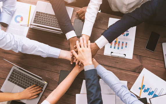Multiethnic business team stacking hands together on meeting