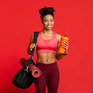 Portrait of happy fitness girl with sporty bag, mat, shaker