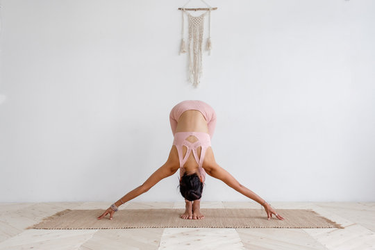 Cute slim young unidentified brunette woman doing yoga uttanasana while standing on rug on the floor in a pink barefoot suit. Young woman is training at home. Places for advertising