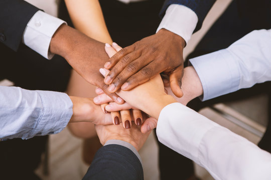 Multiethnic corporate teame stacking hands together in office