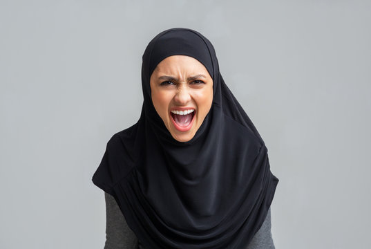 Angry muslim girl in hijab screaming loud, emotionally protesting about something