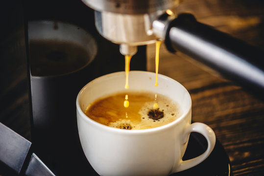 Espresso pours from the coffee machine into a white Cup forming golden foam