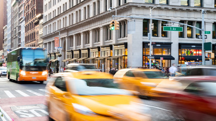 Cars, taxis and buses speed through the busy intersection of 23rd Street and 5th Avenue during a busy afternoon rush hour commute in Midtown Manhattan New York City