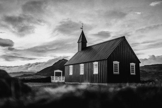 Kirche vor dramatischem Bergpanorama Island