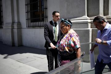 Nobel Peace Prize laureate Rigoberta Menchu followed by Foundation for International Democracy chairman Guillermo Whpei enter at Palacio de la Moneda in Santiago