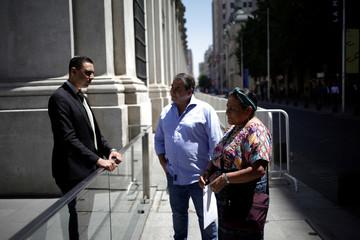 Nobel Peace Prize laureate Rigoberta Menchu and Foundation for International Democracy chairman Guillermo Whpei (C) await to enter at Palacio de la Moneda in Santiago