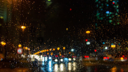 rain drops on the window surface and colorful traffic bokeh