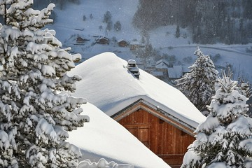 House roof covered with falling snow in a beautiful mountain scenery, idyllic winter atmosphere