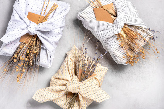 Idea for gift wrapping. Gifts are wrapped in textiles and decorated with dry lavender flowers and wheat, top view, flat lay. Eco-friendly gift wrapping concept, plastic free, zero waste.