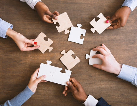 Group of business people assembling jigsaw puzzle together