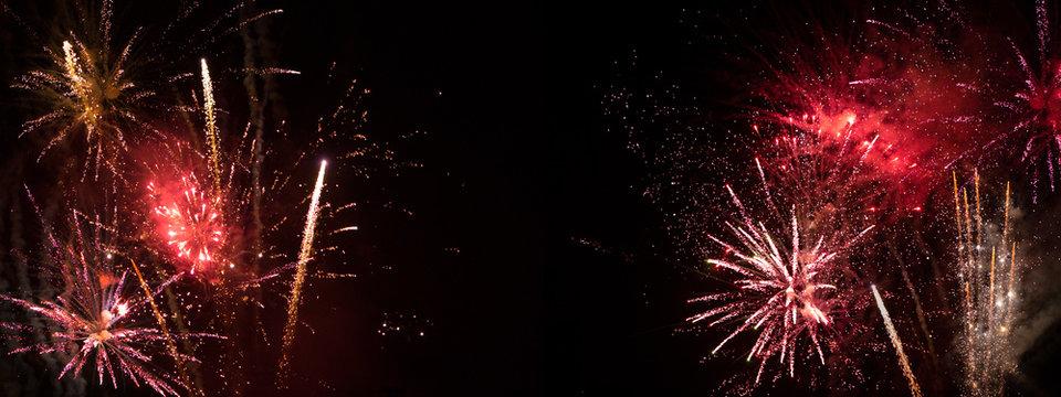 Rotes Feuerwerk vor schwarzem Nachthimmel -Hintergrund für Neujahr und Silvester