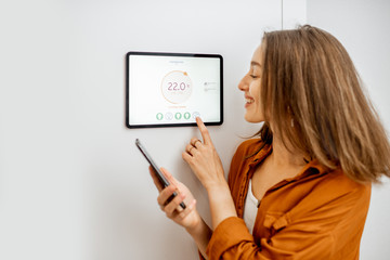 Young woman controlling temperature in the living room with smart phone and digital touch screen panel. Concept of heating control in a smart home
