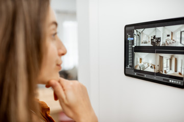 Young woman watching video from security cameras on a digital tablet at home. Concept of remote video surveillance over the internet with smart devices