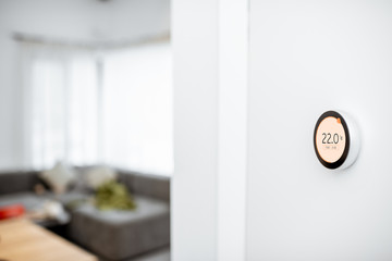 Round smart thermostat with touch screen installed on the wall indoors. Smart home heating regulation concept. View with copy space