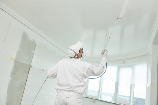 Painter worker with airless painting sprayer covering ceiling surface into white