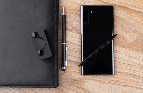 Smartphone with three cameras, notebook, stylus, pen and headphones on a wooden table close-up.