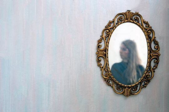 The reflection of a woman in a antique golden mirror in the vintage interior, old pattern wallpaper background