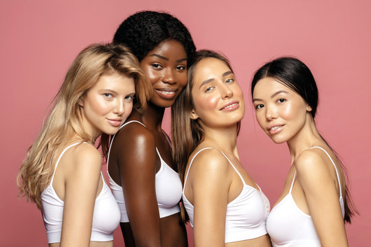 Multi racial Ethnic Group of Womans with diffrent types of skin standing together and looking on camera. Diverse ethnicity women - Caucasian, African and Asian against pink background
