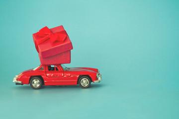 Krasnodar, Russia - December 10, 2019: Red retro toy car delivering  present of red box