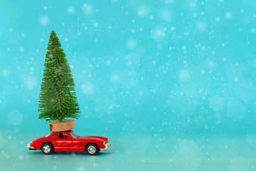 Krasnodar, Russia - December 10, 2019: Red toy car with a christmas tree on the roof, blue background.
