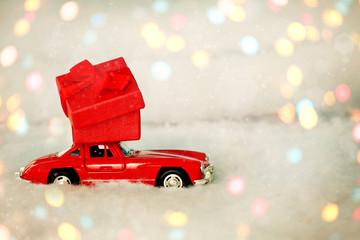 Krasnodar, Russia - December 10, 2019: Red retro toy car delivering  present of red box on white backgr