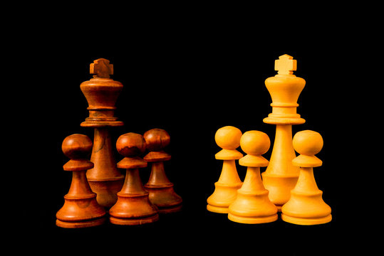 Black vs White. Two hostile groups opposing each other. Divide et impera (Divide and Rule) concept. Standard chess wooden piece on black background