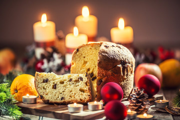 Delicious panettone on christmas table wit decorations and advent wreath and candles