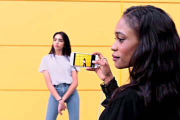 Interracial friends pretty Arab teen and African-American girl using their smartphones to take pictures
