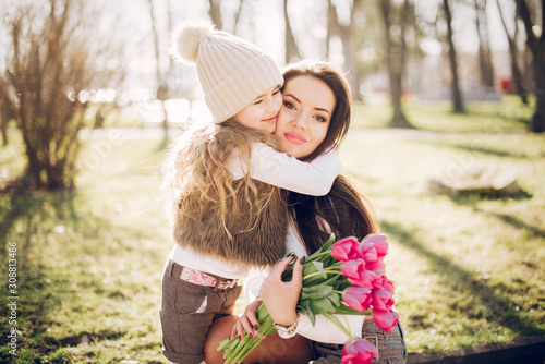 Fashionable mother with daughter. Family in a spring park. Mother's day