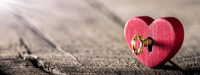 Small Rustic Red Heart With Shiny Golden Key Standing On Wooden Table - Valentine's Day Concept