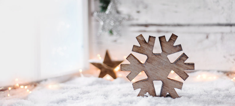 Scandinavian styled christmas background - a big wooden snowflake on a bright white snowy scene beside a window