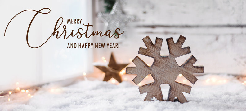 Scandinavian styled christmas background - a big wooden snowflake on a bright white snowy scene beside a window / greeting card text