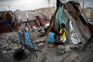 A woman combs the hair of another woman at the entrance of a makeshift shelter at La Saline neighbourhood in Port-au-Prince