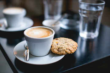 cup of coffee and cookie on a table