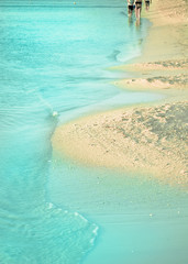 Wall Mural - Tropical beach coastline with clear blue water, sand and people in the distance