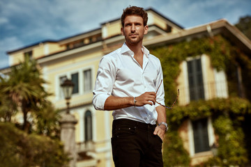 Handsome young man in front of luxury home villa