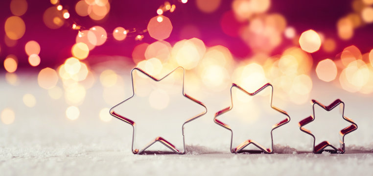Star shaped cookie cutter, pink Background and funky, golden light Bokeh - Merry Christmas!