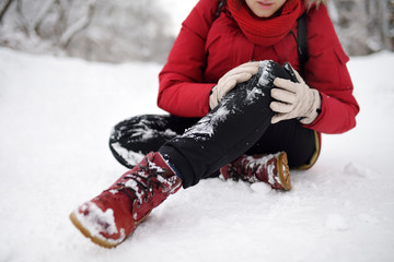 Shot of person during falling in snowy winter park. Woman slip on the icy path, fell, injury knee and sitting in the snow.