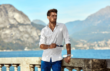 Portrait of handsome man in elegant white shirt standing near the lake in the alps