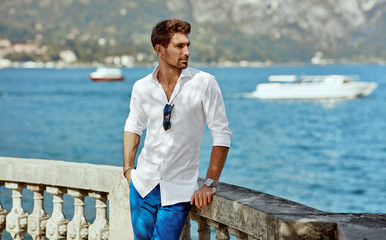 Handsome young man wearing elegant white shirt and posing outdoor near the river in alps