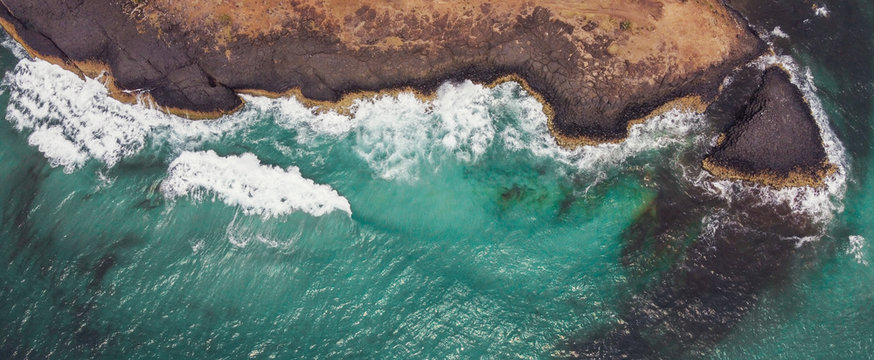 Aerial view of aqua sea waves breaking on rocky cliff, adventure summer travel vacation, perseverance and resilience concept, decarbonisation concept