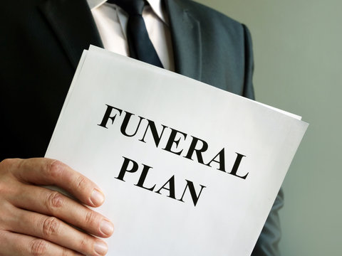 Man holds Funeral plan and stack of papers.