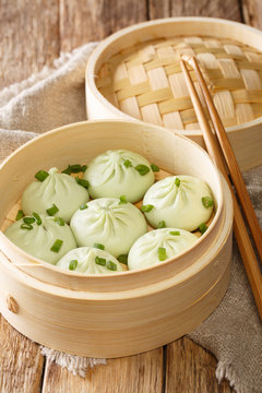Traditional chinese baozi steam buns in a bamboo steamer basket close-up on the table. Vertical