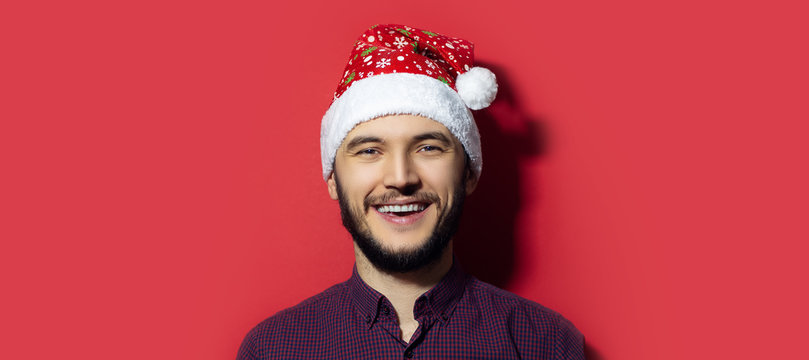 Portrait of young smiling man wearing Christmas hat with snowflakes isolated on red background.