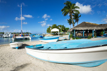 Fototapete - Caribbean beach with wooden boats and catamaran with unrecognizable people having fun