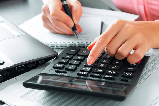 Female accountant in the office uses a calculator and writes data in a notebook. Profit analysis, taxes and payments calculations, preparation of financial statements concept