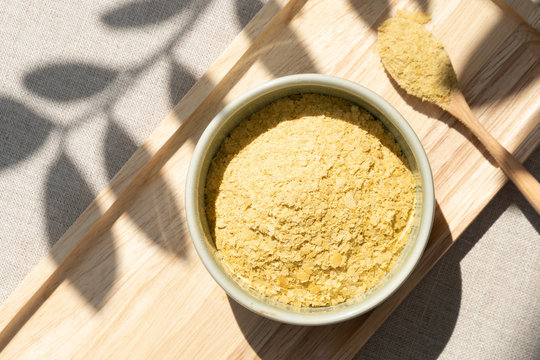 Top view & Closeup, Yellow flakes of nutritional yeast in ceramic bowl and wooden spoon, excellent source of vitamins, minerals, and high-quality protein for plant-based diet / vegan food.