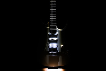 White electric guitar. Neck and fingerboard of musical instrument. Creative style with light shadows. Wall mural