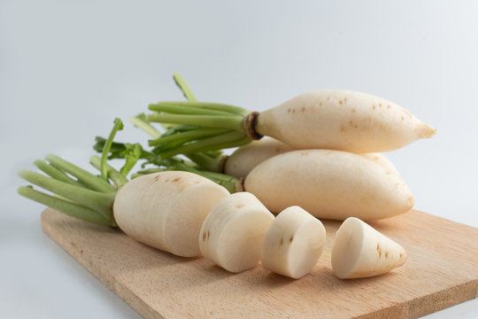 White radish on a wooden cutting board, white background